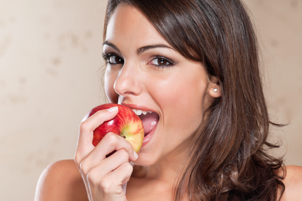 Pretty young woman eating an apple