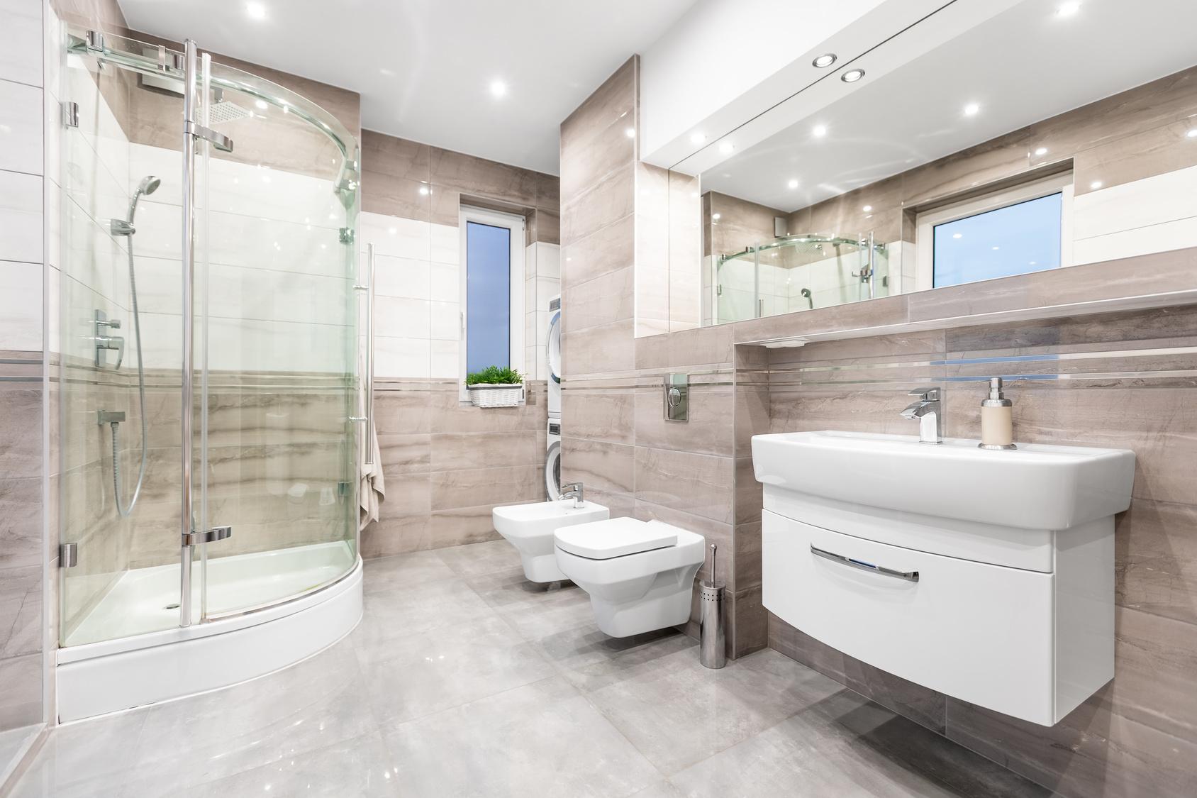 Modern beige bathroom with window, walk in shower, toilet, bidet, basin and large mirror