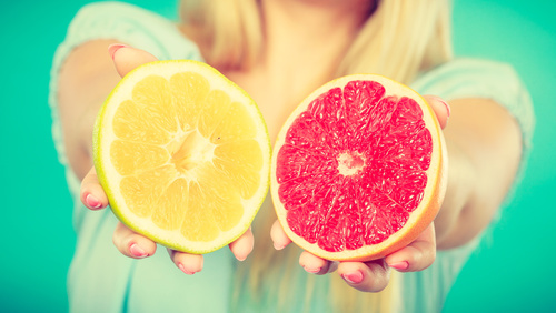 Halfs of yellow red grapefruit citrus fruit in human hands
