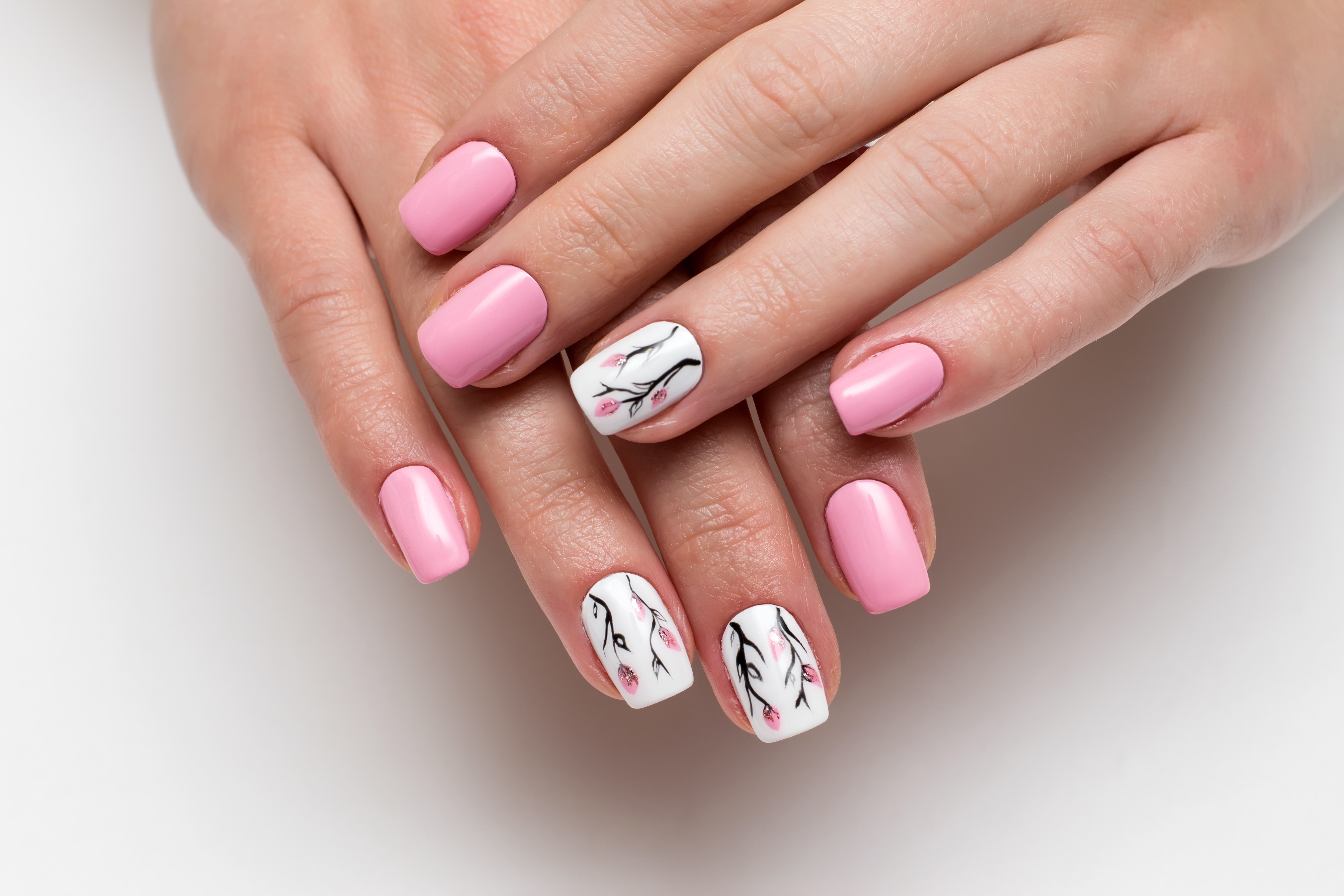delicate pink manicure with spring flowers on short square nails on a white background